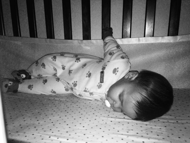 Holding onto his crib.